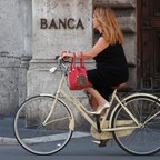 A woman rides a bike past a bank in Italy.