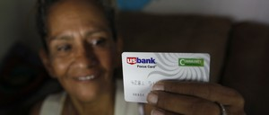 A woman holds up a debit card.