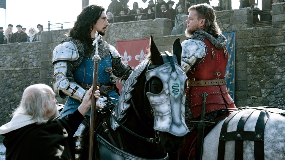 Adam Driver and Matt Damon are seen in armor, on horseback, staring each other down