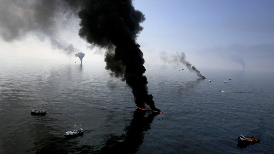Black smoke billows from multiple points on an ocean expanse.
