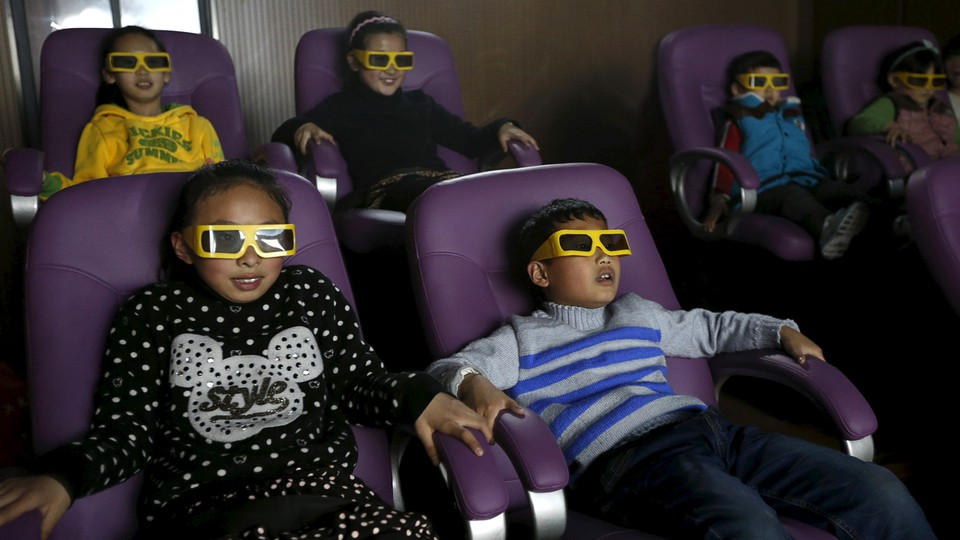 Children sit in purple movie-theater chairs, wearing disposable 3-D glasses.