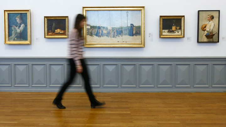 A woman, who is blurry, walks past a series of paintings in a museum.