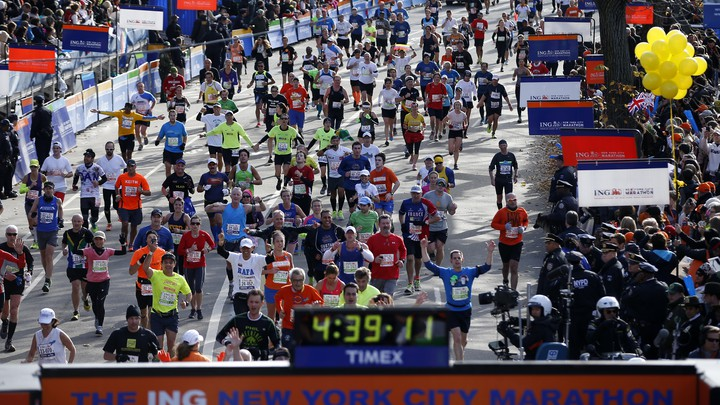 Runners approach the New York City Marathon finish line, where a clock reads 4:39:11