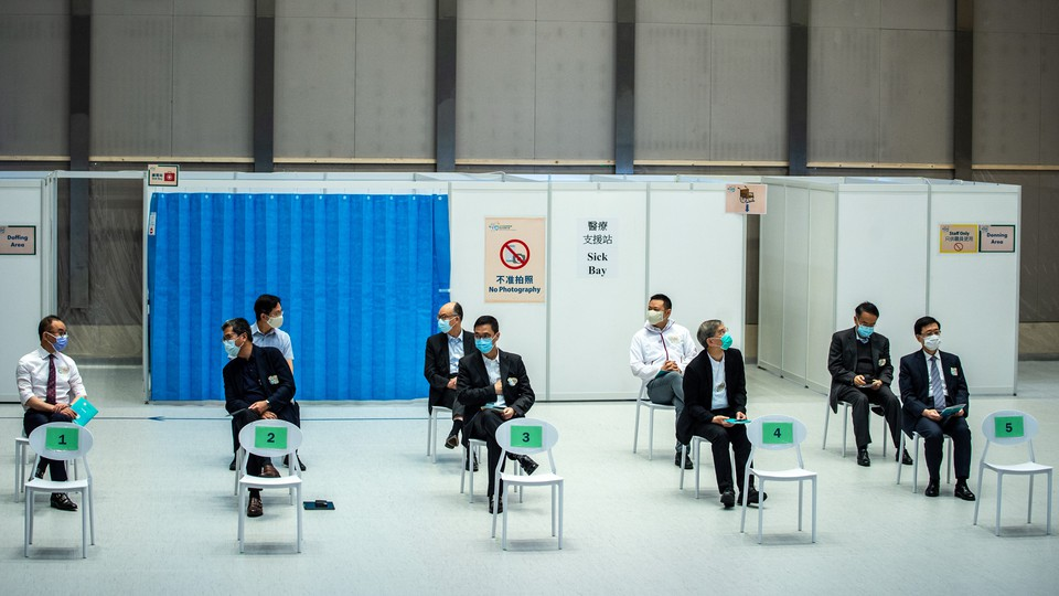 Hong Kong government officials sit in socially distanced chairs to get the second jab of the Sinovac vaccine.