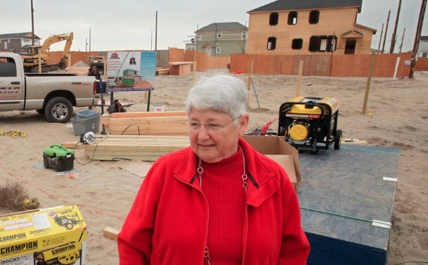 A woman stands in front of a construction site.