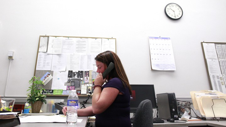 A woman uses an office phone at a desk.