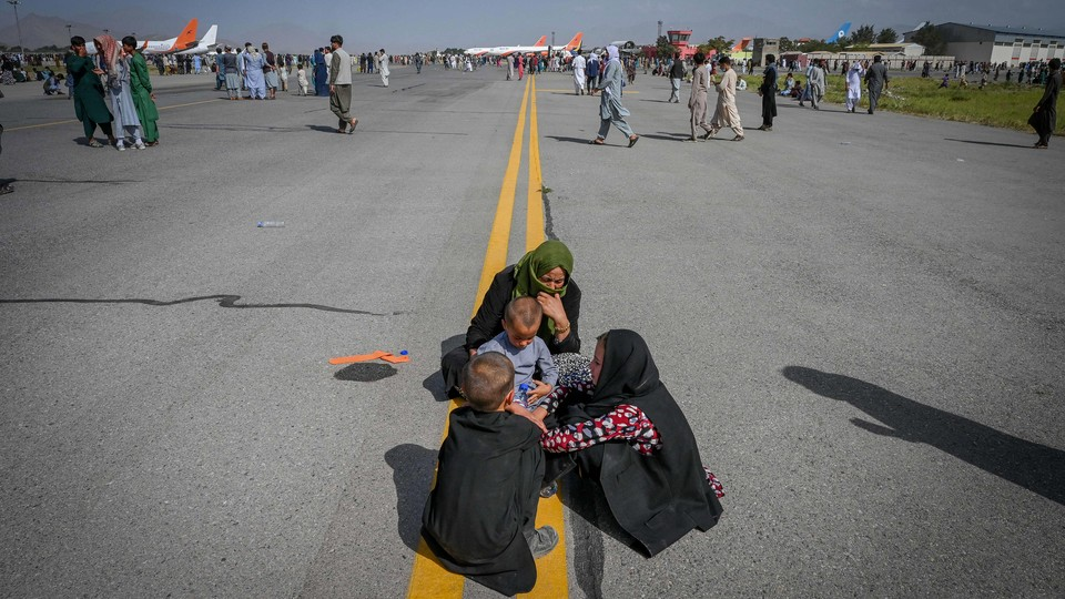 Afghan people waiting on the tarmac at the Kabul airport.
