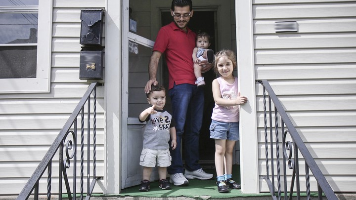Mohammad Zkrit and three of his four children stand on the porch of their newly-rented home in Erie, Pennsylvania. The family fled the ongoing civil war in Syria and have been resettled in the United States.