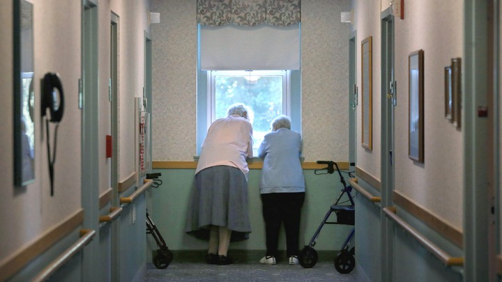 Two nursing-home residents look out a window.