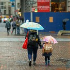 rear view of a woman and child on a city street with umbrellas