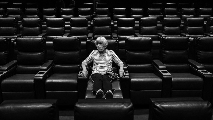 A woman sits alone in an empty movie theater