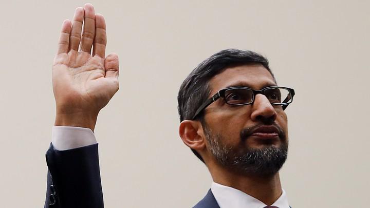 Sundar Pichai raises his right hand.