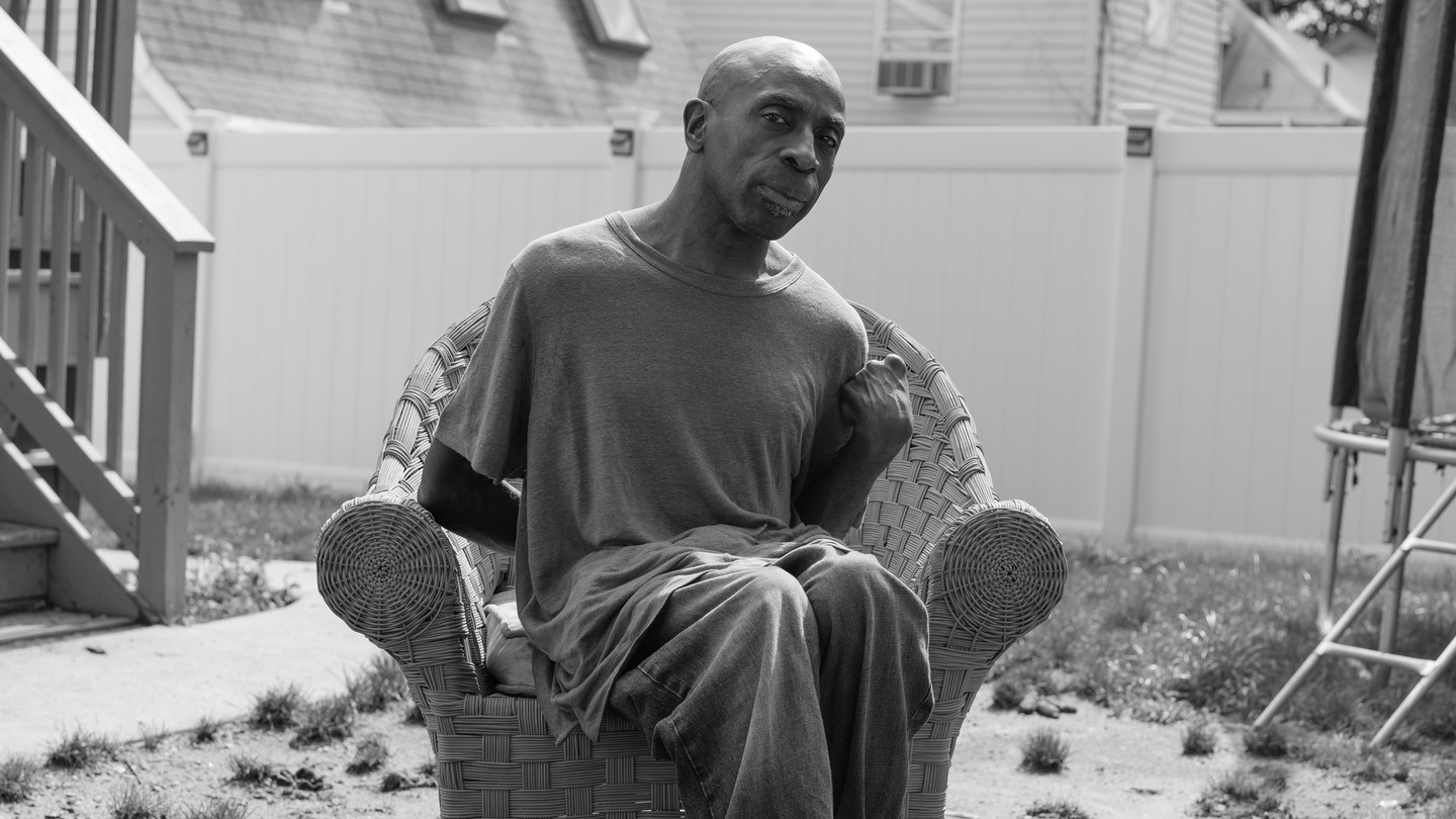 A black-and-white photograph of Keith Jones sitting in a wicker chair in the sun, in a yard covered with sparse clumps of grass
