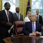 A photo of Donald Trump in the Oval Office, with HUD Secretary Ben Carson.