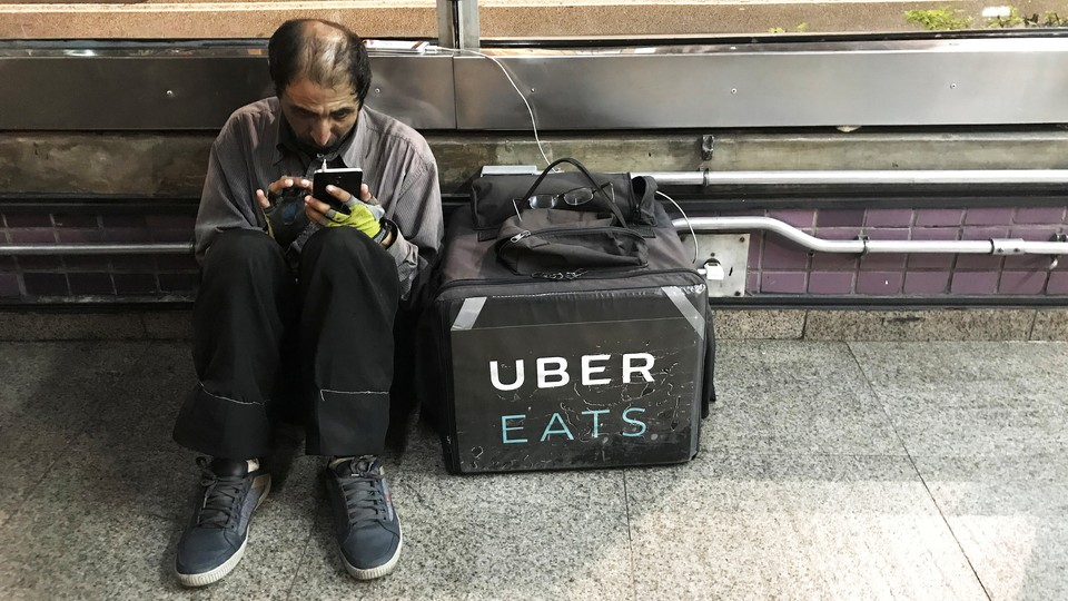 An Uber Eats worker checks his mobile phone in São Paulo.
