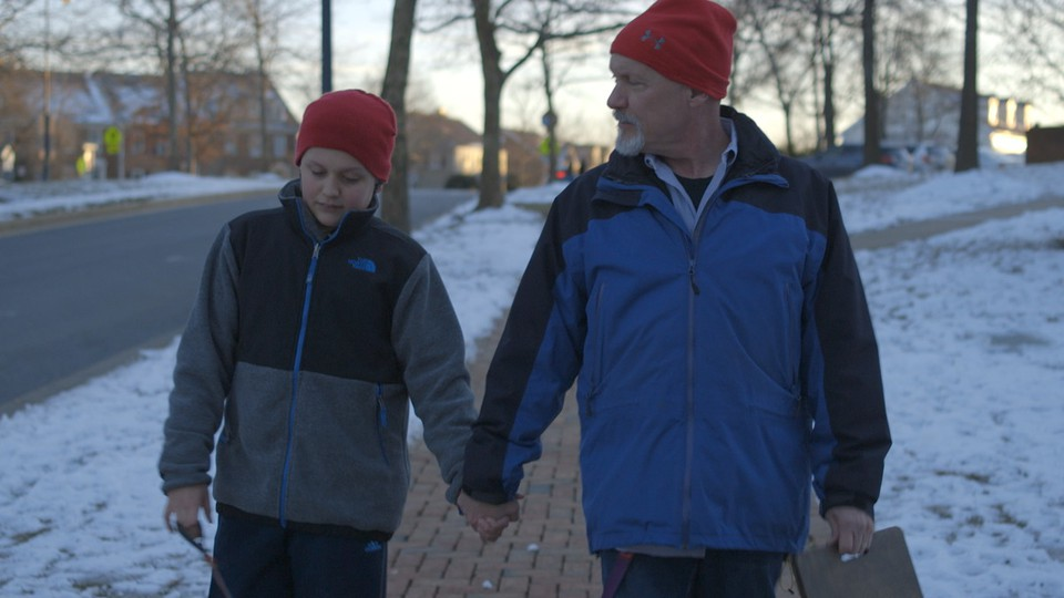 A boy and his father walk along a snowy street holding hands