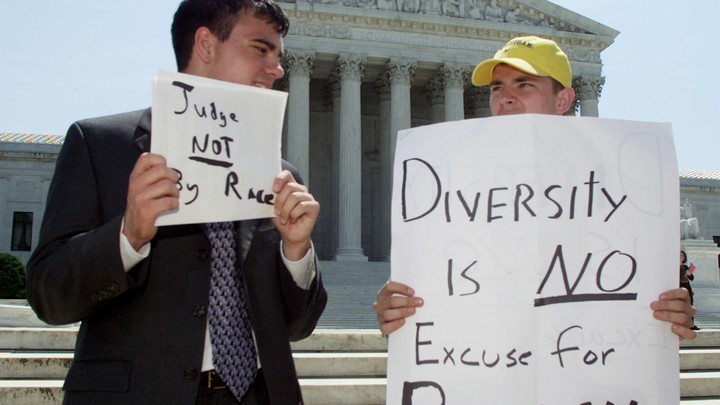 Two male students protest outside of the Supreme Court with signs accusing affirmative action of being racist.