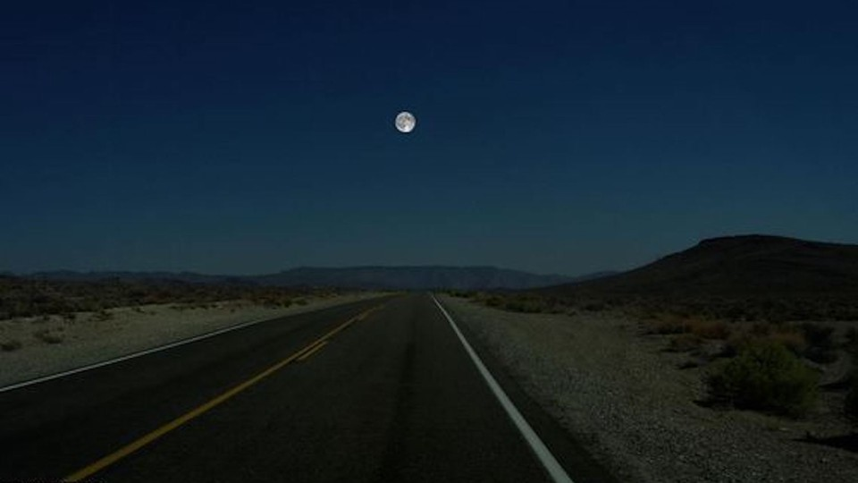 A photograph of a deserted road through a desert valley, with the full moon hanging in the sky.