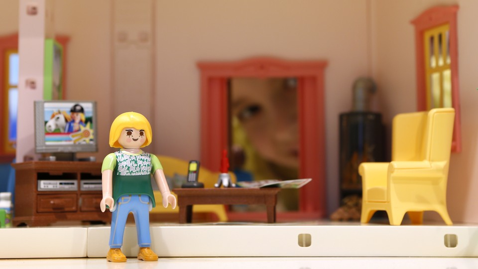 A Playmobil doll sits in her tiny, plastic living room.