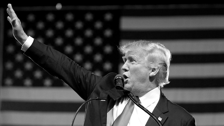 A black-and-white photo of President Donald Trump shows him waving as he stands behind a podium.