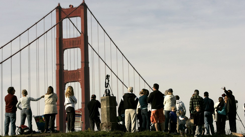 People gather on a hill in view of the Golden Gate Bridge
