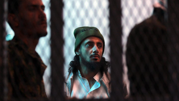 A suspected al-Qaeda militant stands behind bars.