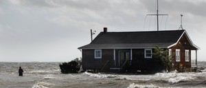 A man walks away from a building that has been surrounded by water pushed up by Hurricane Sandy in Bellport, New York.