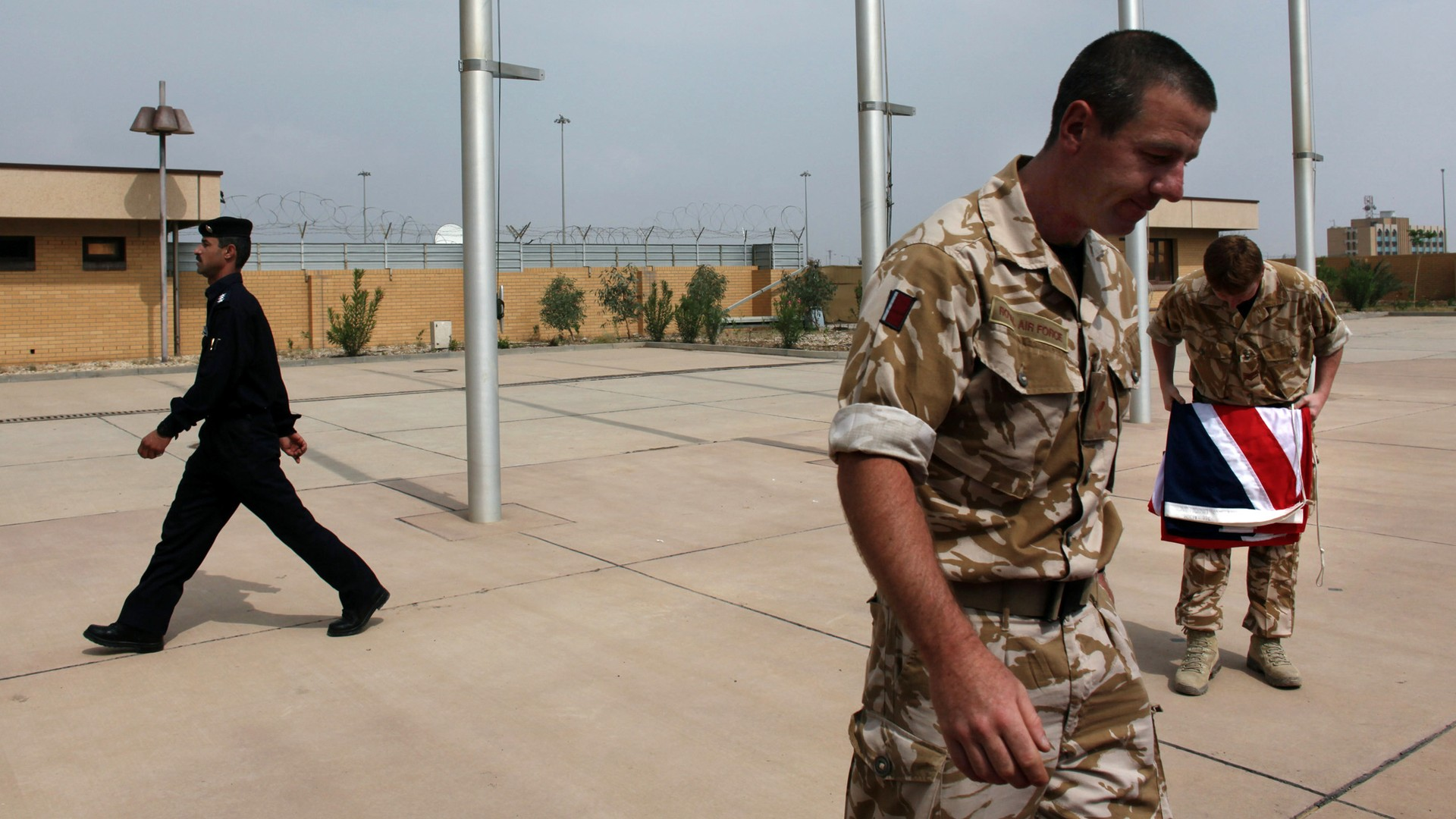 An Iraqi policeman walks past two British military officers, one folding the Union Jack.