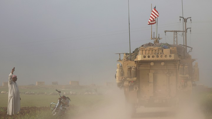 A man gestures at U.S. military vehicles driving in the town of Darbasiya in Syria.