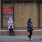 A pedestrian wearing a protective face mask walks past a boarded up building in San Francisco, California, U.S., on Tuesday, March 24, 2020. Governors from coast to coast Friday told Americans not to leave home except for dire circumstances and ordered nonessential business to shut their doors.