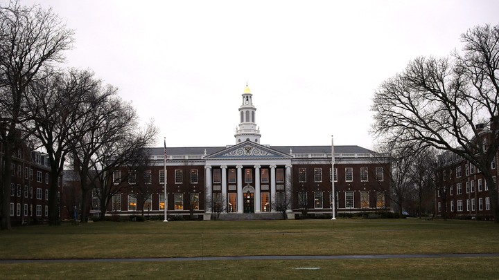 A library at Harvard is shown from afar with the lawn stretching in front of it
