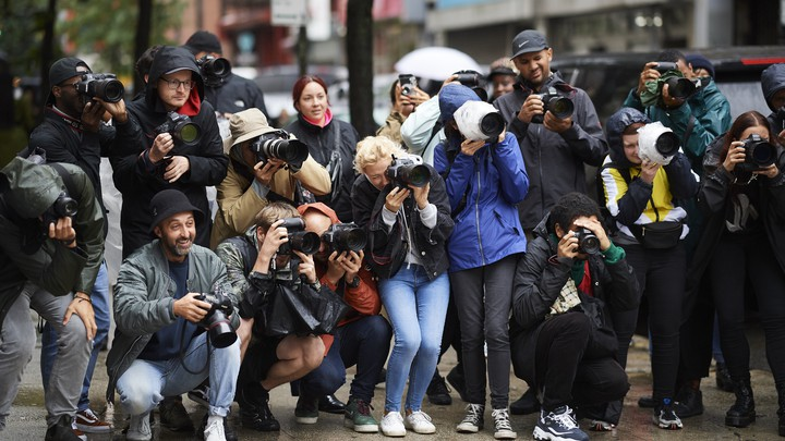 A crowd of paparazzi on the sidewalk