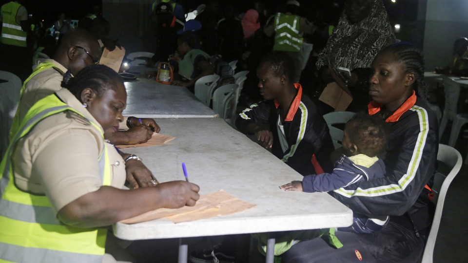 Nigerian returnees wait as Nigeria immigration officials fill out their return forms on folding tables.