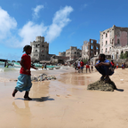 Children playing on a beach in Mogadishu surrounded by small fishing boats and historic ruins.
