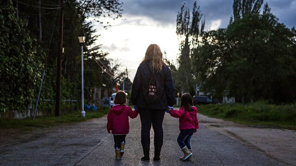A mom with two children holding her hands.