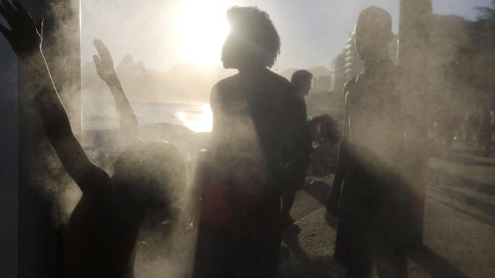 People cool off at a cooling station on a hot winter day on Ipanema beach.