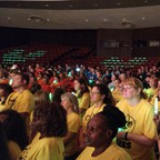 Hundreds of Charlottesville teachers stand in an auditorium for their back to school convocation.