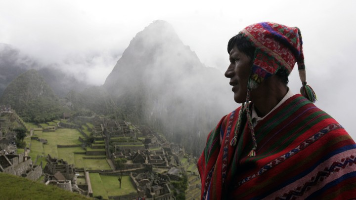A Quechua musician stands next to the Machu Picchu.