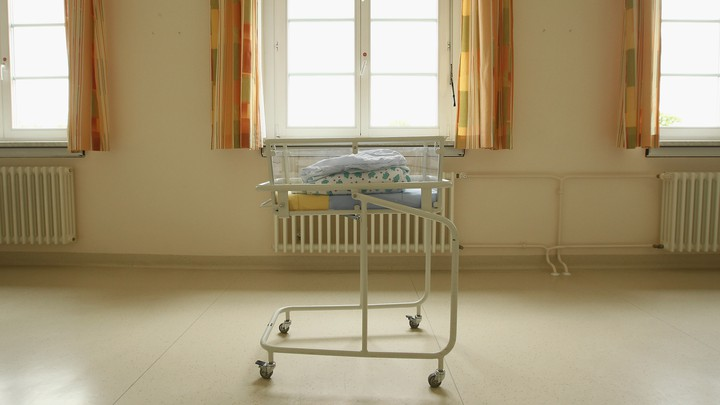 Folded blankets sit atop a cart for newborn babies.