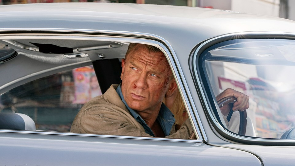 James Bond, played by Daniel Craig, looks out of the window of a car.