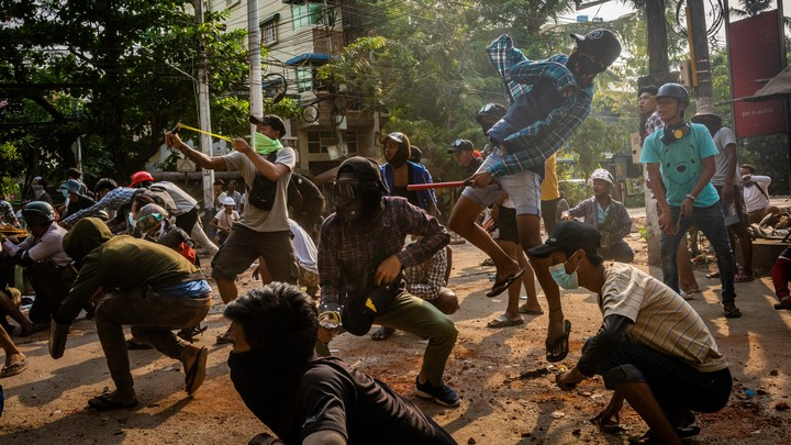 Masked protesters use slingshots and pelt stones.