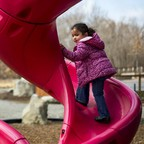 A child on a pink slide in an urban park.