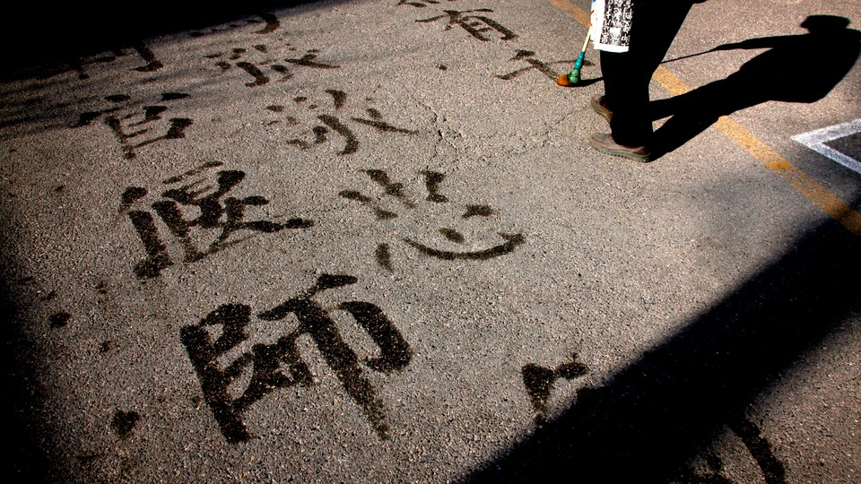 A man writes Chinese characters on a footpath using water and a brush in central Beijing.