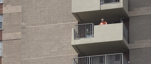 A resident of New York's high-rise housing project Co-op City looks out from his apartment balcony.
