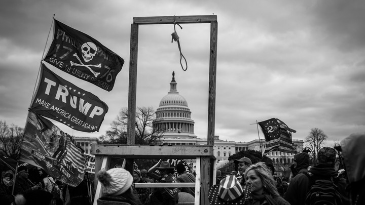 A crowd of Trump supporters surround a newly erected set of wooden gallows outside the Capitol Building.