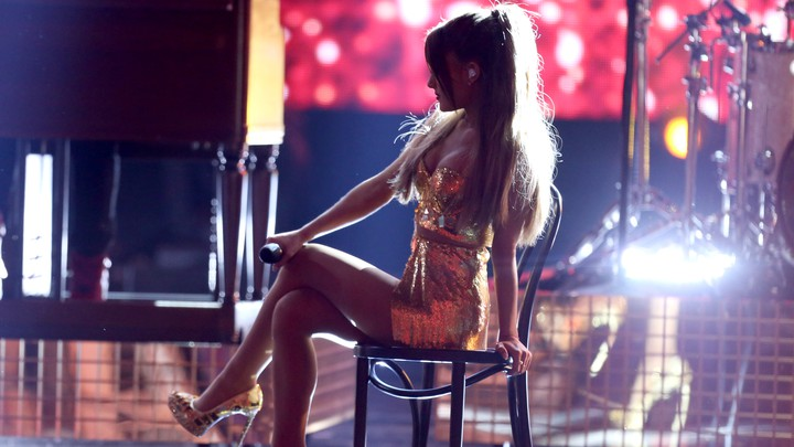 Ariana Grande sits onstage on a chair in partial shadow.