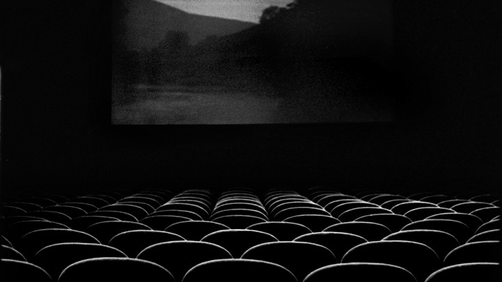A black and white image of an empty movie theatre with a scenic location on screen