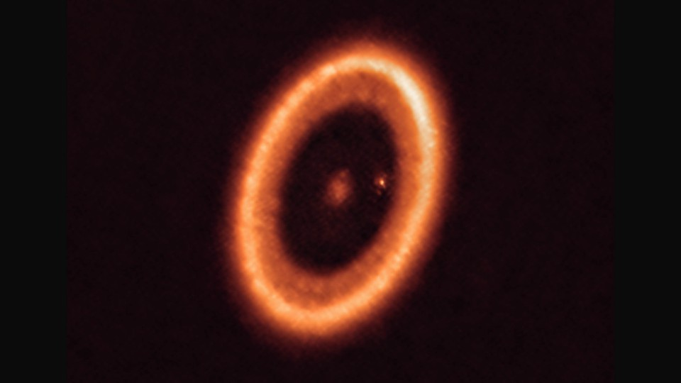 The exoplanet PDS 70c seen as a speck of light within a bright circle, surrounded by a circumplanetary disk