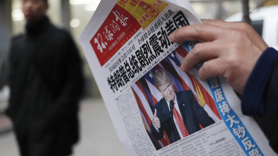 """A man reads a newspaper with the headline of """"U.S. President-elect Donald Trump delivers a mighty shock to America"""" at a news stand in Beijing."""