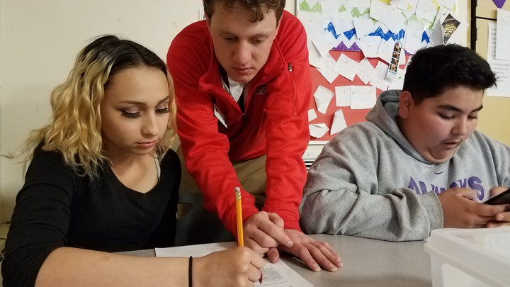 A teacher leans over two students, one of whom is holding a pencil and writing on a worksheet.